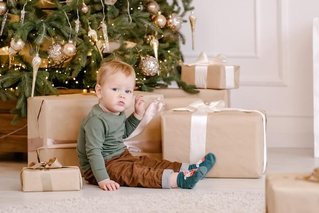 Милый маленький мальчик сидит под елкой с подарочной коробкой.