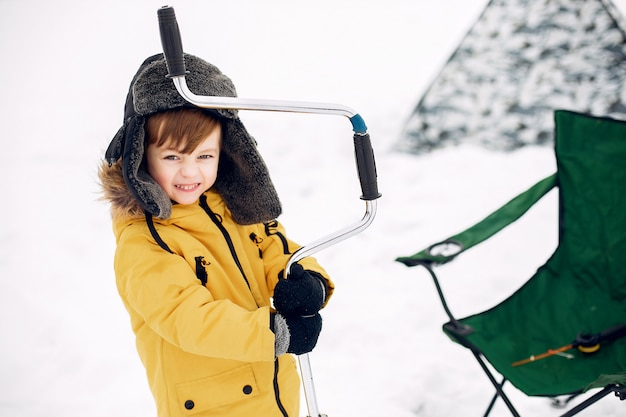 Cute little boy sitting on a winter fishing