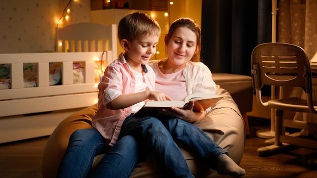 Милый маленький мальчик сидит с матерью ночью и читает книгу сказок на ночь. концепция воспитания детей и семьи, проводящей время вместе в ночное время.