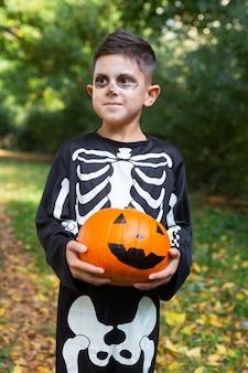 Cute little boy in skeleton costume holding pumpkin