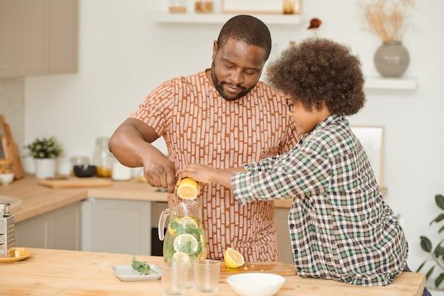 레모네이드와 함께 주전자에 레몬 주스를 짜내는 귀여운 소년