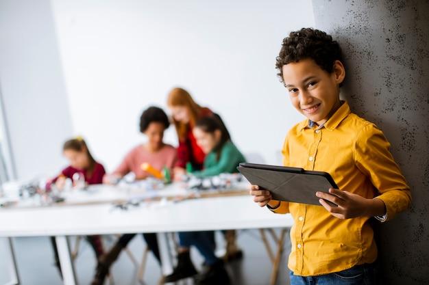 로봇 교실에서 전기 장난감과 로봇을 프로그래밍하는 아이들의 그룹 앞에 서있는 귀여운 어린 소년