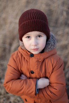 Cute little boy stands in the open air.