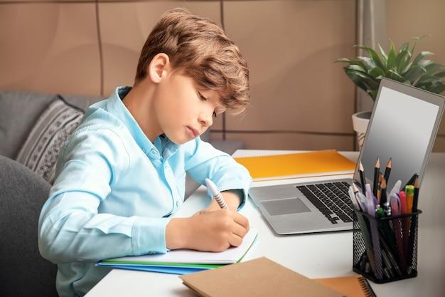 집에서 공부하는 귀여운 작은 소년. 온라인 교육의 개념
