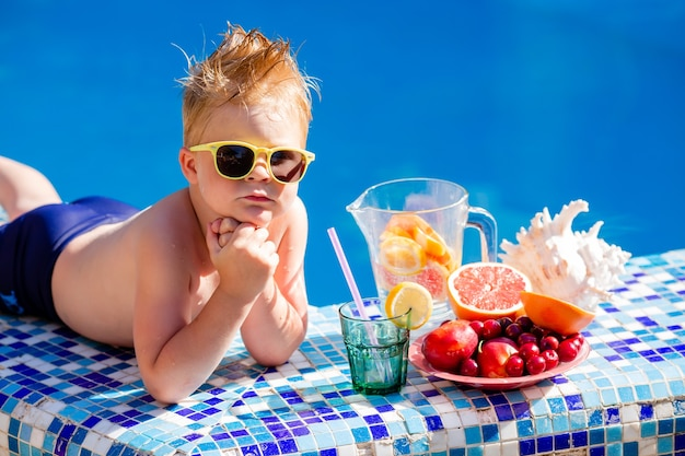 Cute little boy in sunglasses and swimsuit drinks lemonade by the pool.