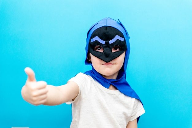 Cute little boy in a superhero costume on a colored wall