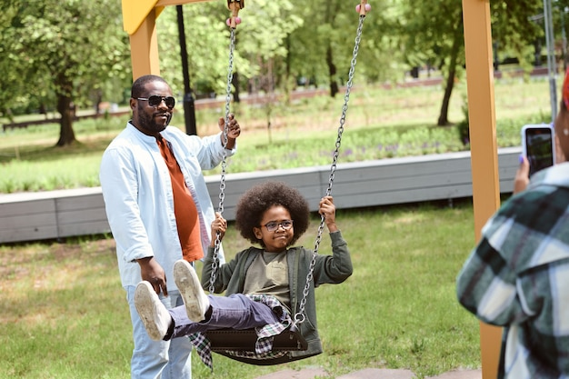 Милый маленький мальчик качается в парке, пока его мать фотографирует его