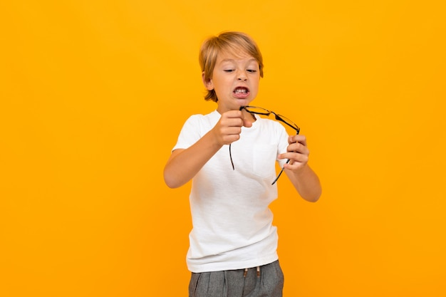 Cute little boy in t-shirt and trousers holds a glasses isolated on yellow background