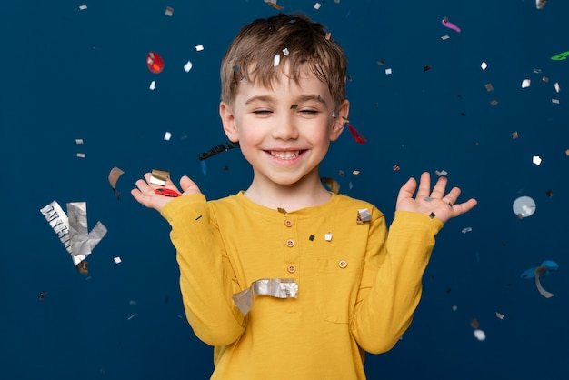 Милый маленький мальчик, бросающий конфетти