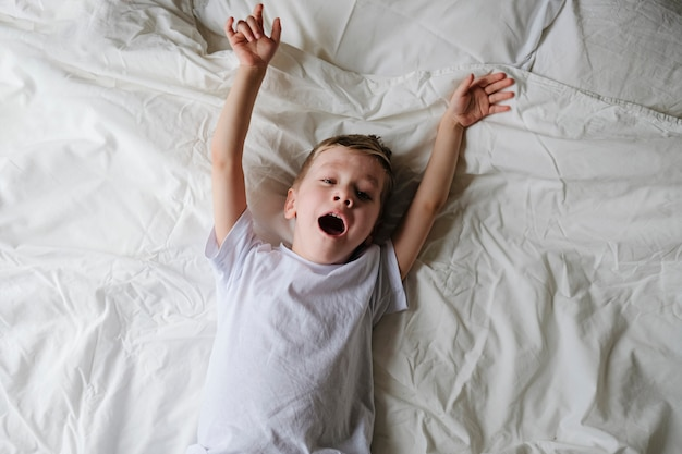 Cute little boy toddler wakes up, yawning and stretching on a bed in a bedroom.