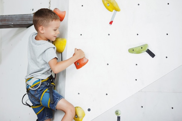 Милый маленький мальчик тренируется на стене для скалолазания в помещении