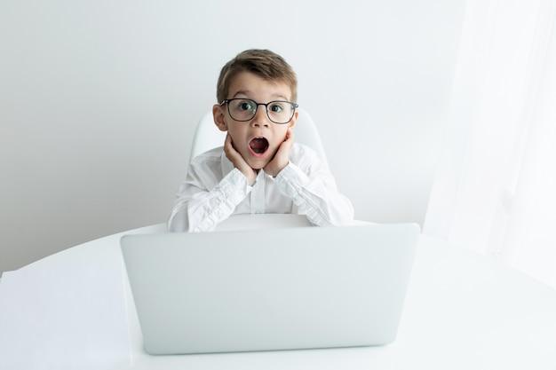 Cute little boy using laptop while doing homework against white