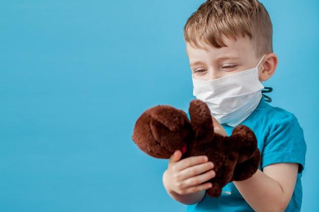 Милый маленький мальчик с помощью небулайзера на синем фоне. концепция аллергии