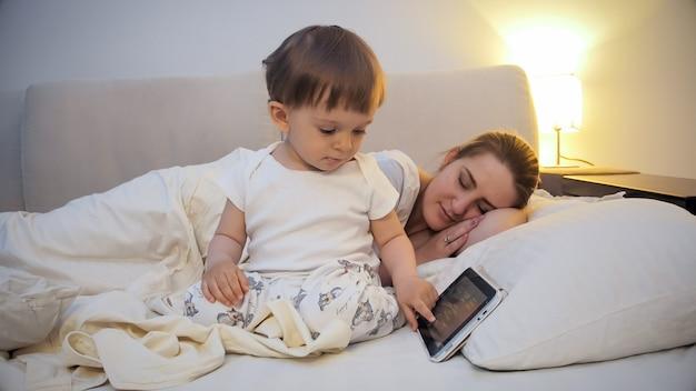 母親がベッドで寝ている間にタブレットコンピュータを使用してかわいい男の子。