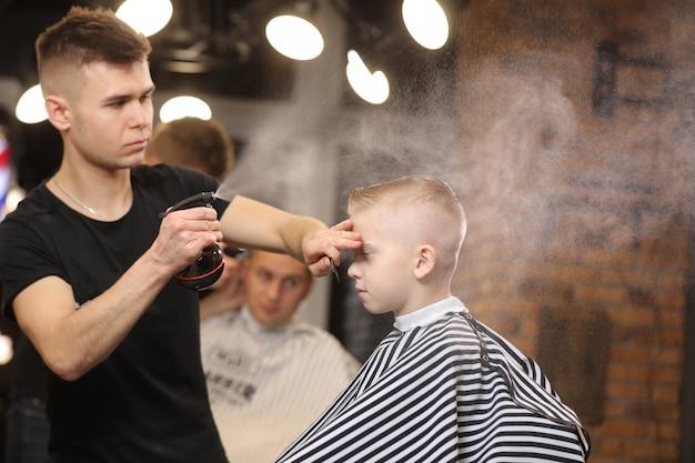 Cute little boy visiting a barbershop