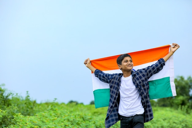 Cute little boy waving indian national tricolor flag over nature background