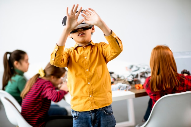 Cute little boy wearing vr virtual reality glasses in a robotics classroom