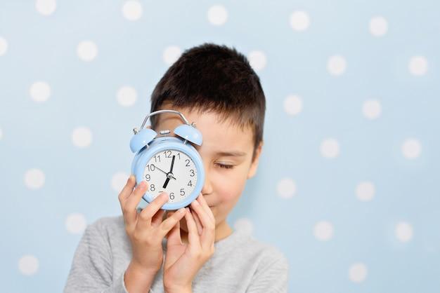 目覚まし時計、人、学校、時間、ライフスタイルのコンセプトとかわいい男の子。眠そうな頭または早い鳥。顔の前で目覚まし時計で眠っている子供。学校に戻る。