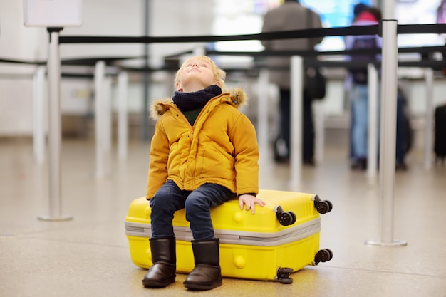 Cute little boy with big yellow suitcase at international airport before flight