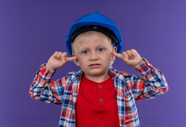 Un ragazzino sveglio con capelli biondi che indossa la camicia a quadri nel casco mantenendo le dita sulle orecchie mentre guarda su una parete viola
