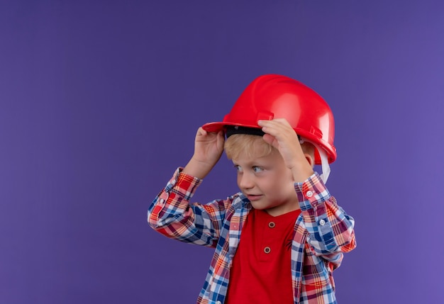 Un ragazzino sveglio con capelli biondi che indossa la camicia controllata che tiene la mano sul casco rosso mentre osserva il lato su una parete viola