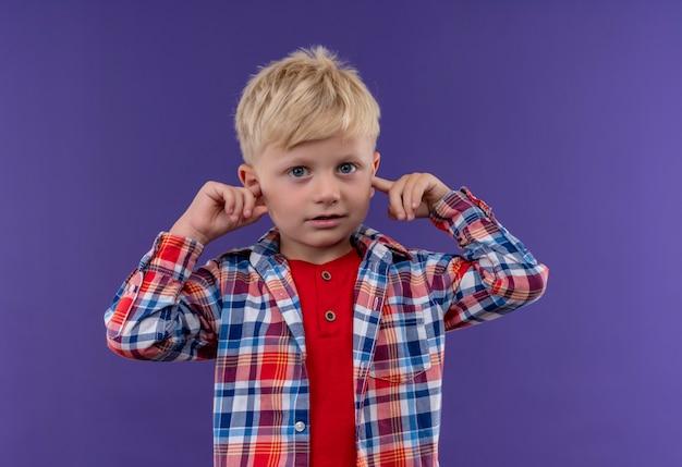 Un ragazzino sveglio con capelli biondi che indossa la camicia controllata mantenendo la mano sulle orecchie su una parete viola