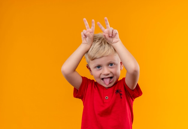 A cute little boy with blonde hair wearing red t-shirt keeping two fingers above his head on a yellow wall