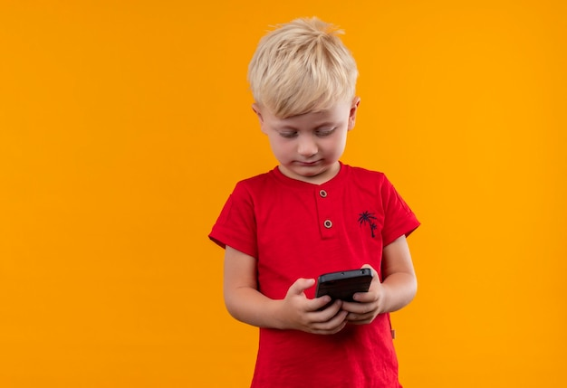 A cute little boy with blonde hair wearing red t-shirt looking at mobile phone on a yellow wall