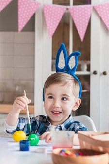 Cute little boy with bunny ears painting easter eggs