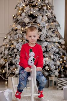 クリスマスツリーの前に木製の馬に座ってクリスマスアクセサリーとかわいい男の子