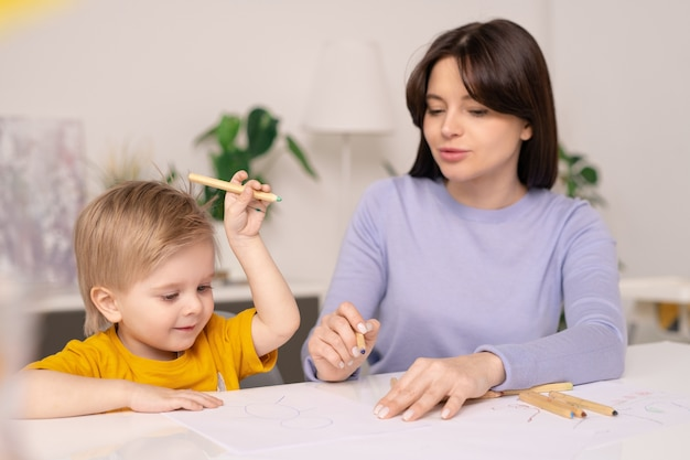 Cute little boy with crayon keeping hand raised over desk with paper while drawing picture and his young mother helping him