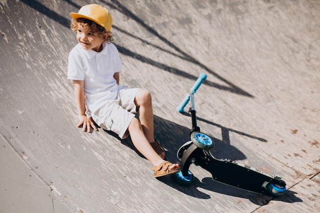Cute little boy with curly hair riding scooter