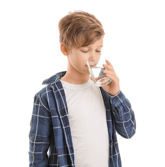 Милый маленький мальчик со стаканом воды на белом
