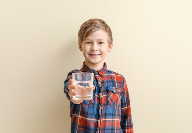 Cute little boy with glass of water on color