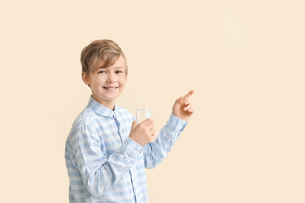 Cute little boy with glass of water pointing at something on color