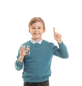 Cute little boy with glass of water and raised index finger on white