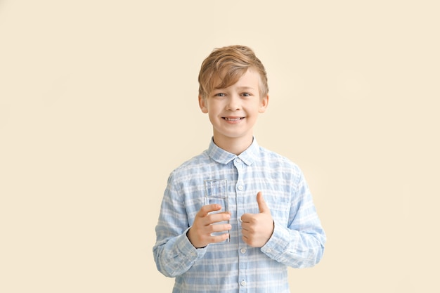 Cute little boy with glass of water showing thumb-up on color
