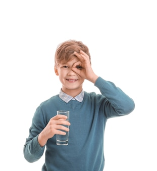 Cute little boy with glass of water on white