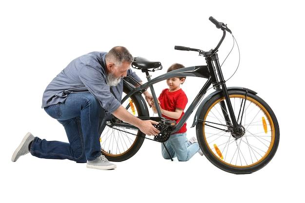 白い背景の上の自転車を修理する祖父とかわいい男の子