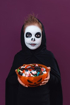 Cute little boy with halloween makeup dressed as a skeleton holding a cup of sweets.