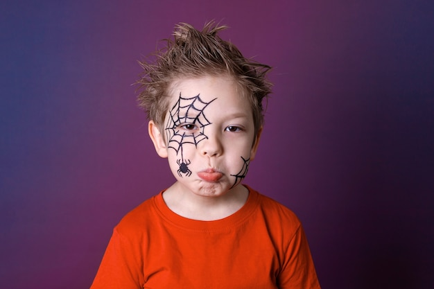 Cute little boy with halloween makeup in gloomy emotions. halloween festive face painting concept.