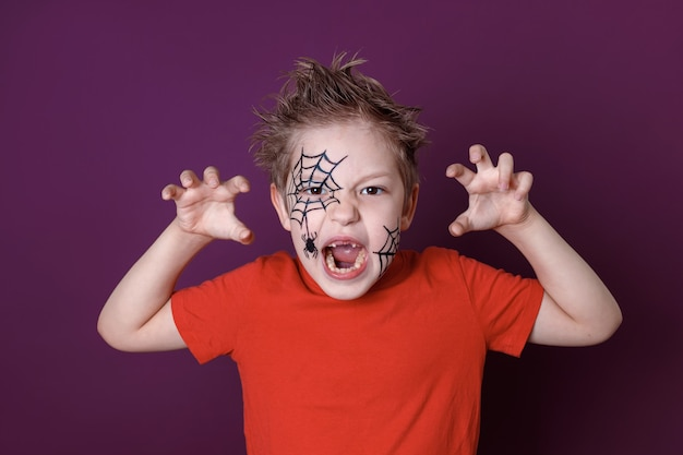 Cute little boy with halloween makeup in red t-shirt scares the camera on a purple background.