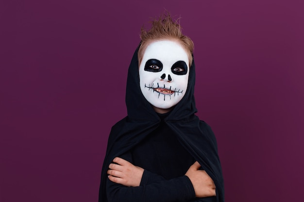 Cute little boy with halloween makeup in skeleton costume. halloween festive face painting concept.