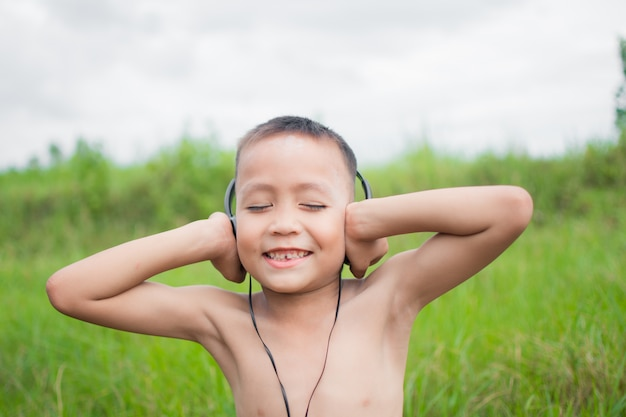 Cute little boy with headphone for listening in the park, her face feel like happy with sunshine. subject is blurry.