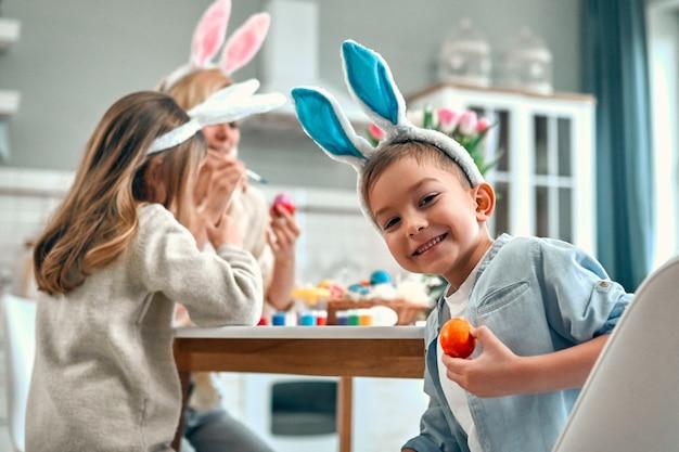 그의 여동생과 어머니와 함께 귀여운 어린 소년 부활절 축하를 위해 준비하고 있습니다. 토끼 귀를 입고 행복한 가족은 계란을 그리는 동안 부활절 전에 함께 시간을 보내고 있습니다.