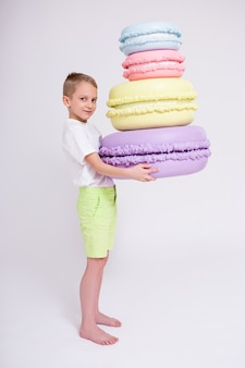 Cute little boy with huge macaroons over white background