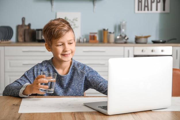 Милый маленький мальчик с ноутбуком питьевой воды дома