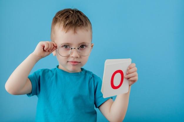 Милый маленький мальчик с письмом. ребенок учится буквы. алфавит