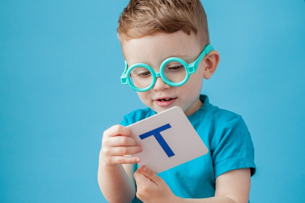 背景に文字とかわいい男の子。子供は手紙を学びます。アルファベット。