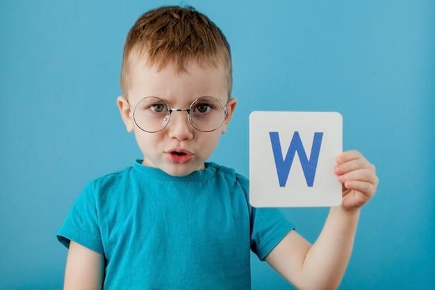 Милый маленький мальчик с письмом на синем фоне. ребенок учится буквы. алфавит